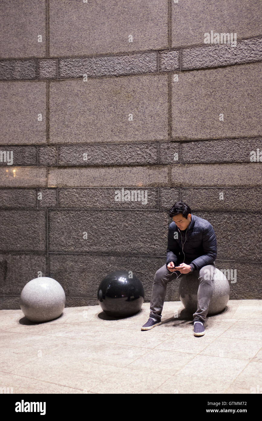 Young man engrossed with his mobile telephone, London, UK - Stock Image