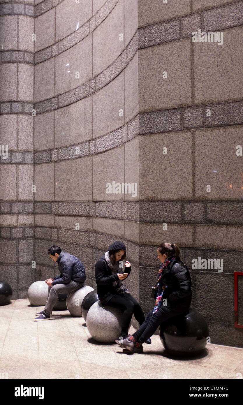 Young people engrossed with their mobile telephones, London, UK - Stock Image