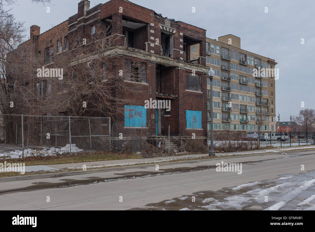 A new apartment/condominium building sits behind an abandoned building in the Brush Park neighbourhood of Detroit, - Stock Image
