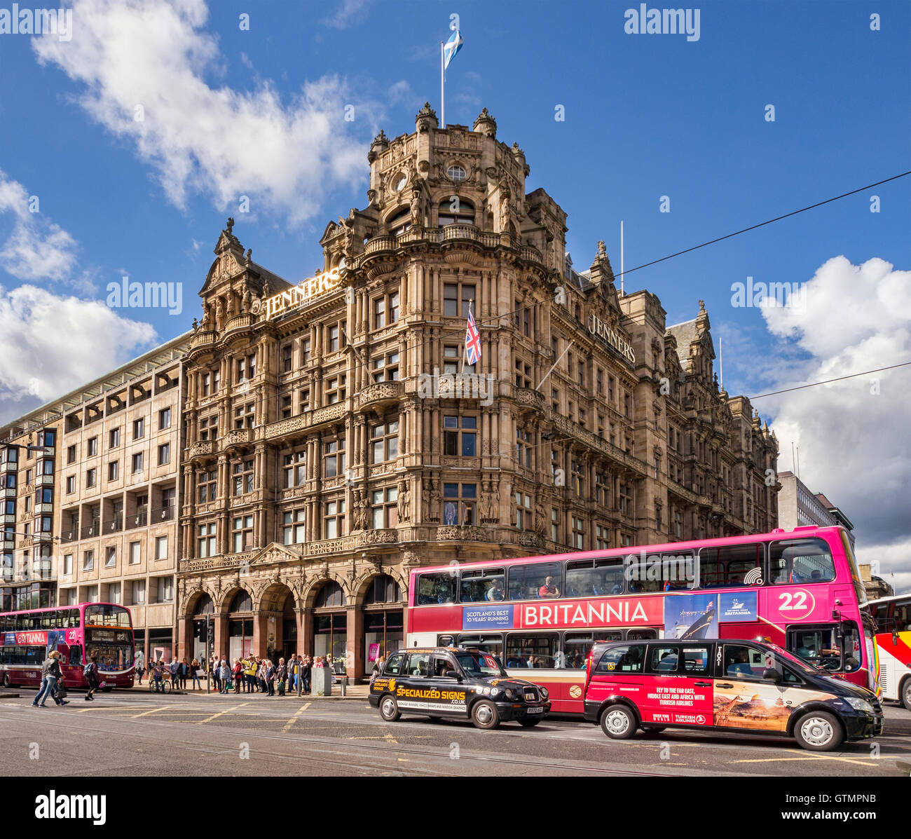 Busy street corner in Princes Street, Edinburgh, with Jenners Department Store, buses,taxis and people, Scotland, - Stock Image