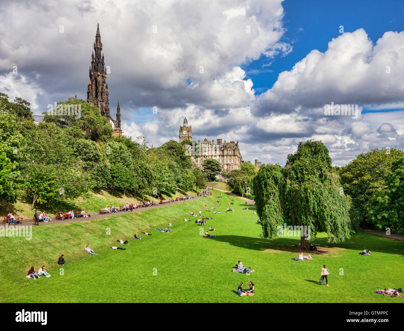 People sunbathing in Princes Street Gardens, Edinburgh, on a fine day in early autumn, with with Scott Monument - Stock Image