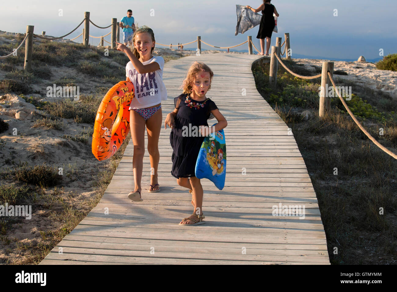 Sa Roqueta Beach and Ses Illetes Beach, Balearic Islands, Formentera, Spain. Funy girls with floats. - Stock Image