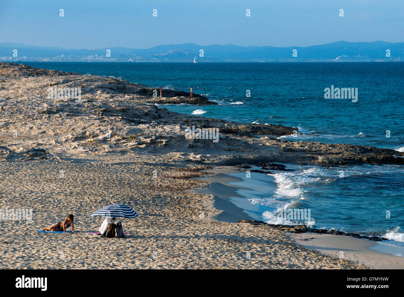 Sa Roqueta Beach and Ses Illetes Beach, Balearic Islands, Formentera, Spain. Nice girl lying in the sand. - Stock Image