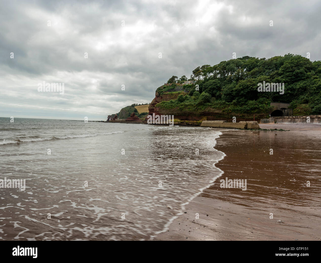 Beautiful landscape depicting storm clouds casting shadows over the South West Coastal Path / beach at Dawlish, - Stock Image