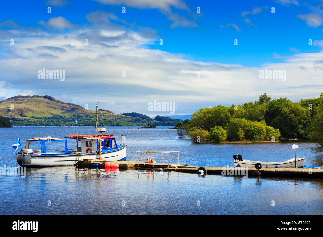 Small ferry at a pier on Loch Lomond, Luss, Scotland, UK - Stock Image