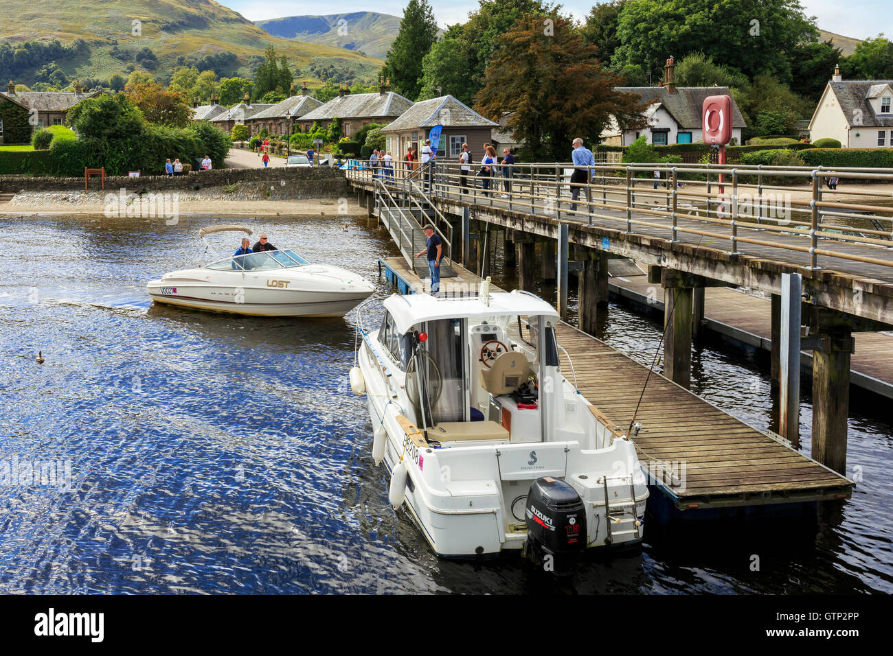 Pier at Luss, Loch Lomond, with two motor boats and tourists, Scotland, UK - Stock Image