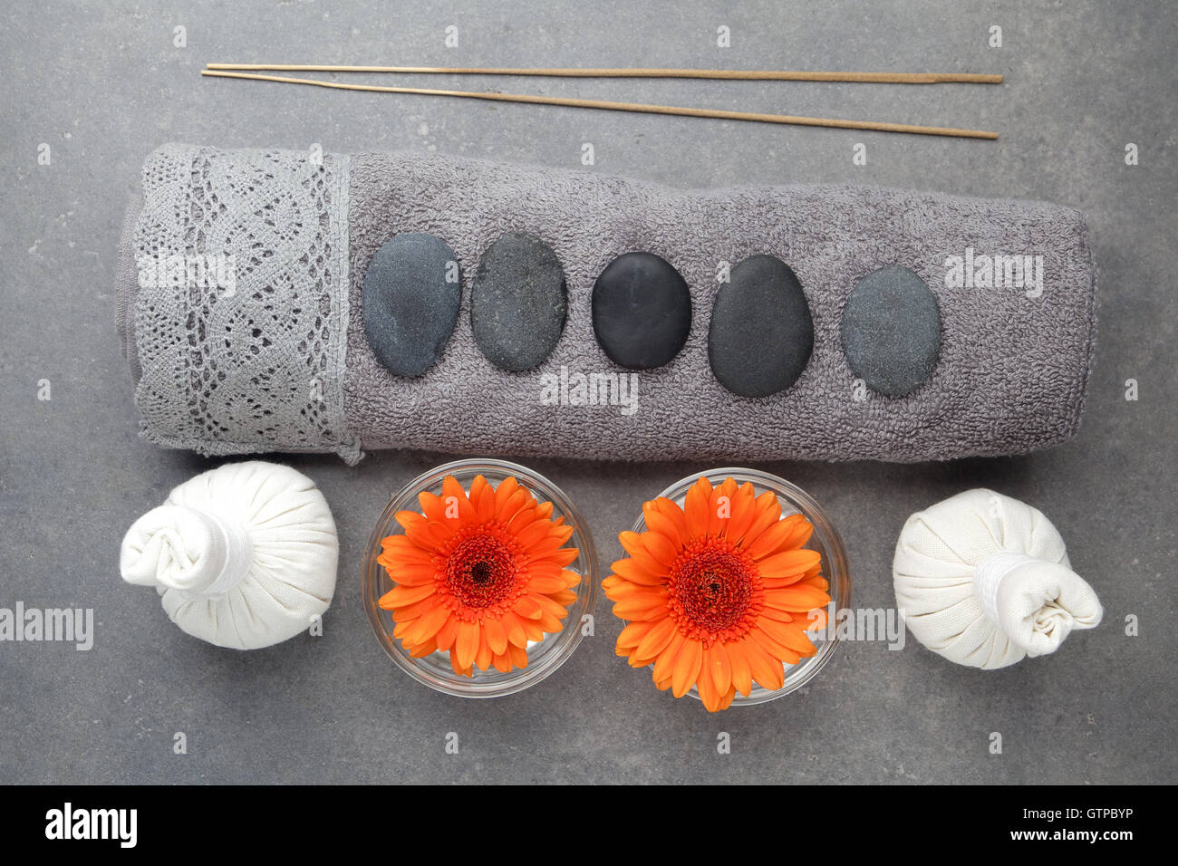 Spa massage setting with rolled towel, thai herbal compress balls and flowers on grey surface - Stock Image