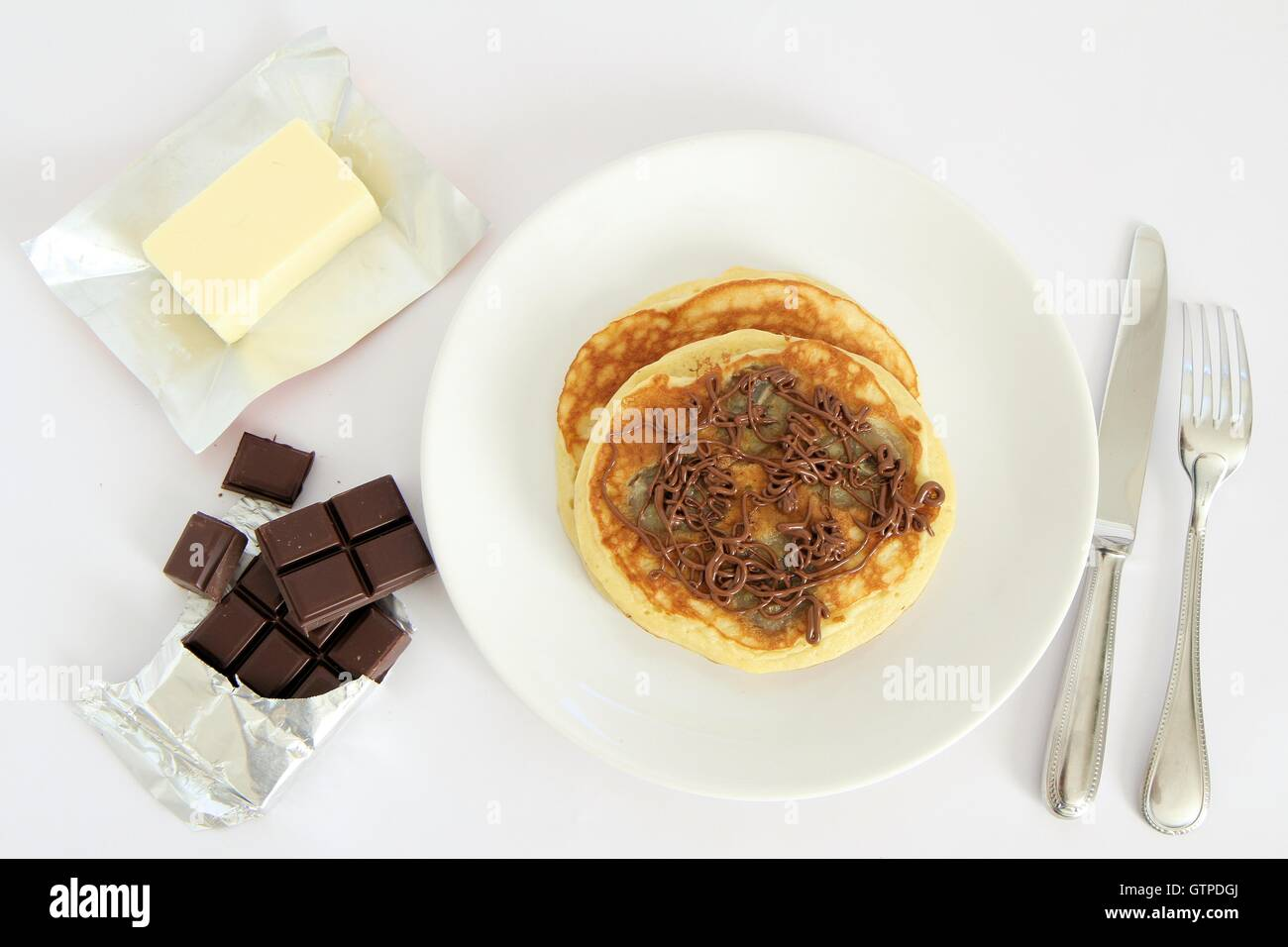 Banana pancakes drizzled with chocalate sauce - Stock Image
