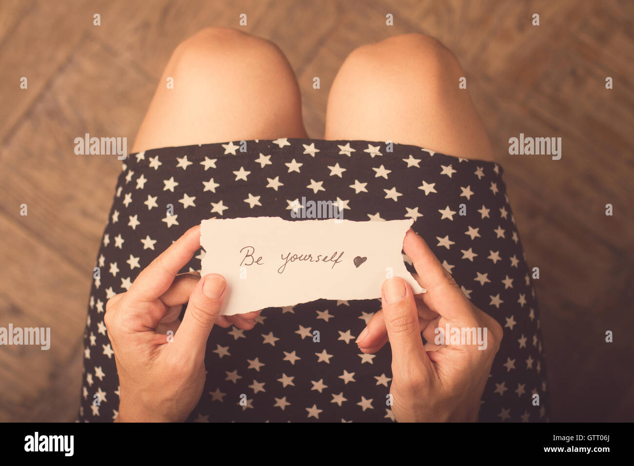 Woman with star patterned dress holding a note with be yourself message on it - Stock Image