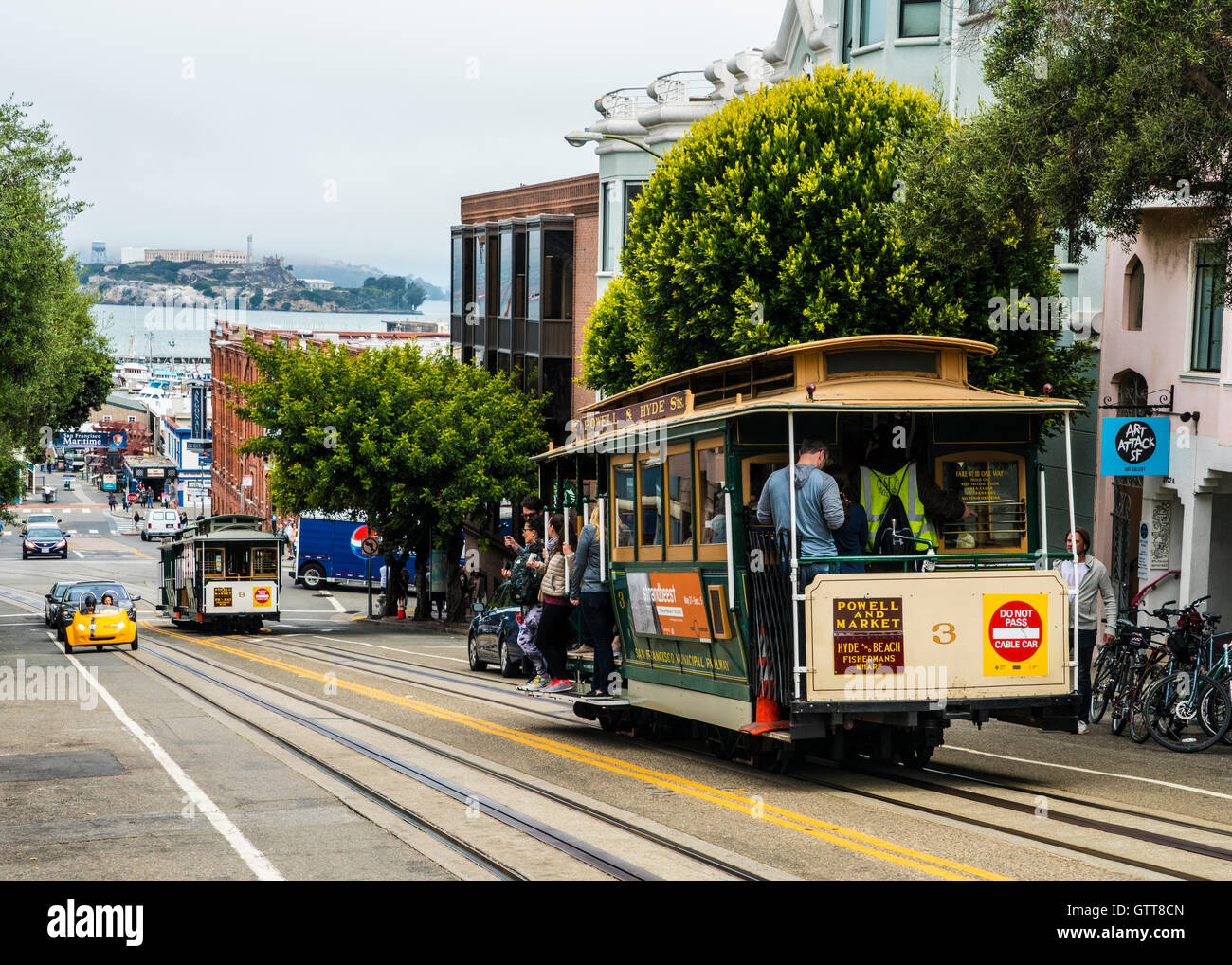 San Francisco cable car on Hyde street with Alcatraz in background - Stock Image
