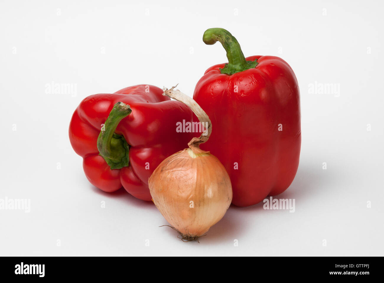 Two red bell peppers and an onion of brown color against white background. Vegetables and food ingredients. Sweet - Stock Image