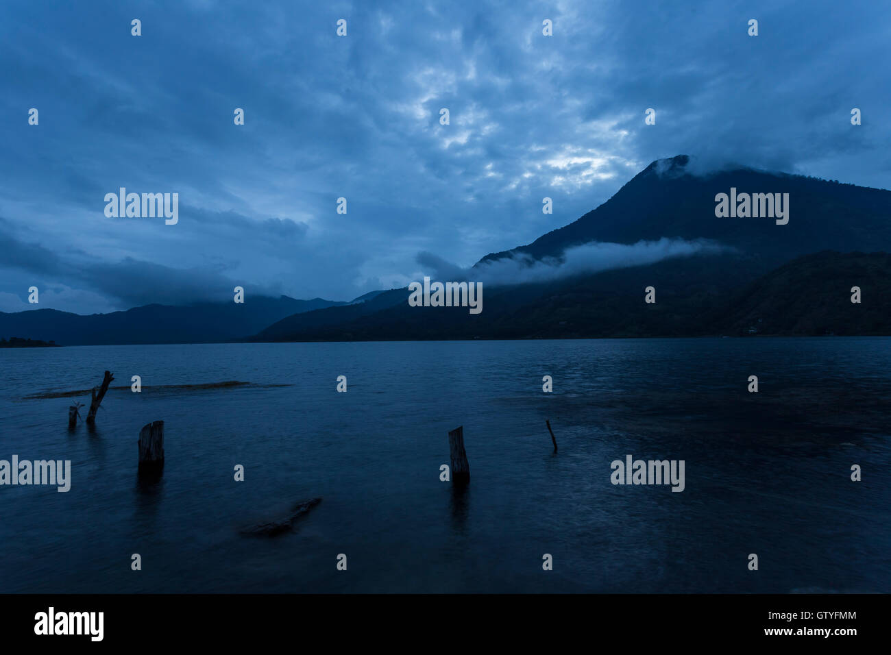 A calm and serene scene of the San Pedro Volcano from Santiago Atitlan at dusk. - Stock Image