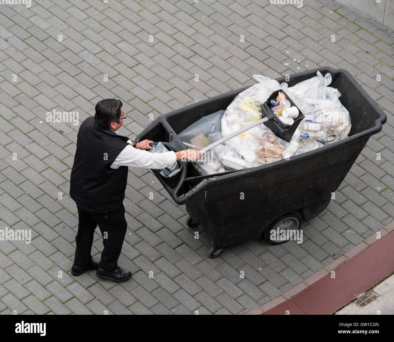 worker picking up trash and bags of garbage high angle overhead view - Stock Image