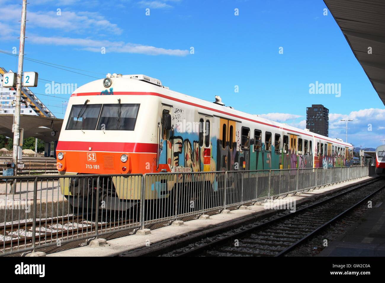 Two car multiple unit passenger train with graffiti covering the livery in the main railway station in Ljubljana, - Stock Image