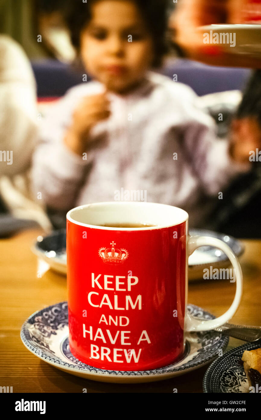 Keep Calm and Have a Brew Sayings on a red Mug with child in the background - Stock Image