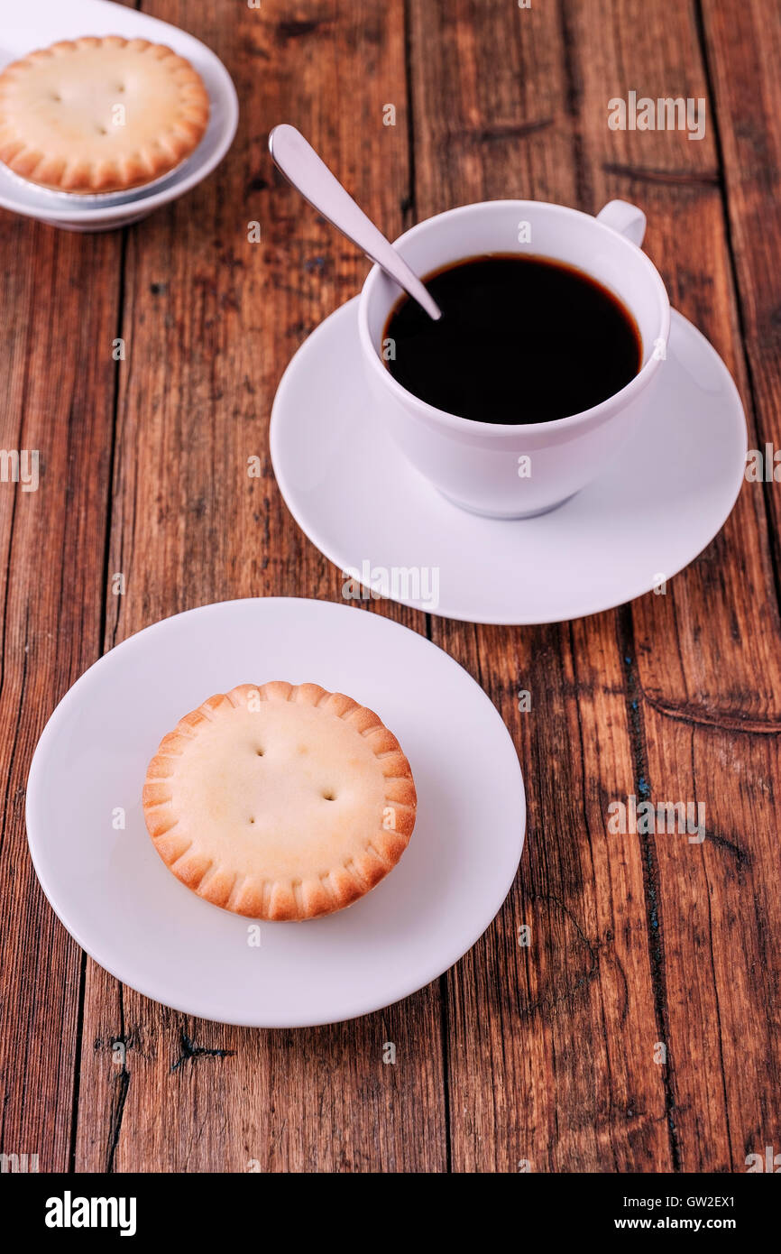 coffee and mince pies for breakfast on a wooden table - Stock Image
