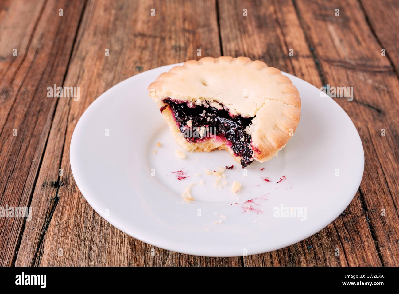 Mince Pies with berry jam inside on a white plate on the wooden table - Stock Image