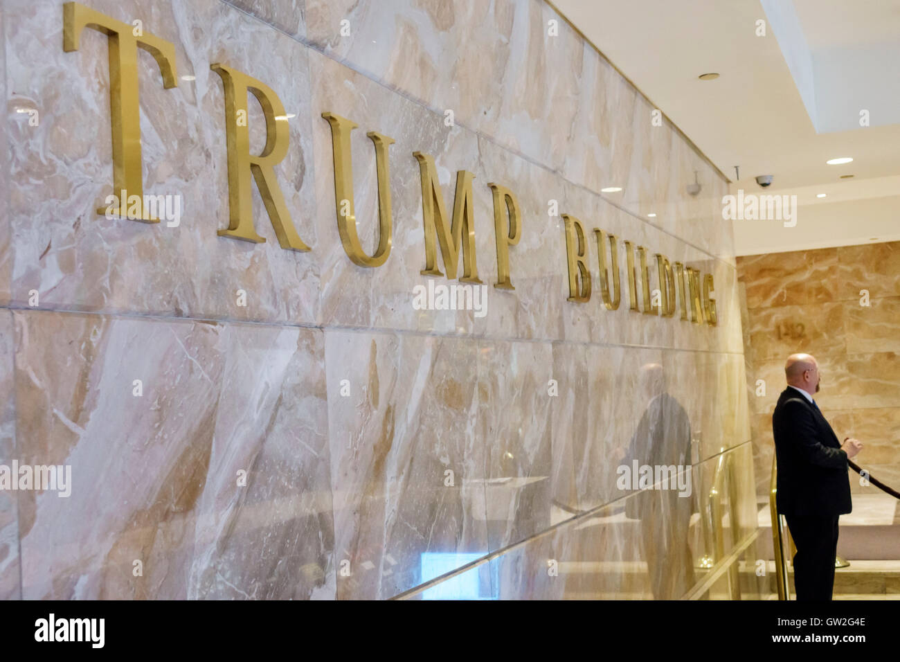 Lower Manhattan New York City NYC NY Financial District Wall Street Trump Building lobby security guard marble sign - Stock Image