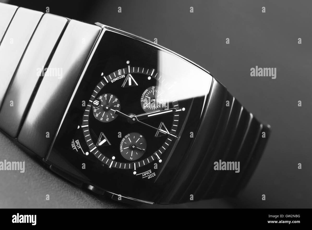 Mens chronograph watch made of high-tech ceramics with sapphire glass over black. Selective focus - Stock Image