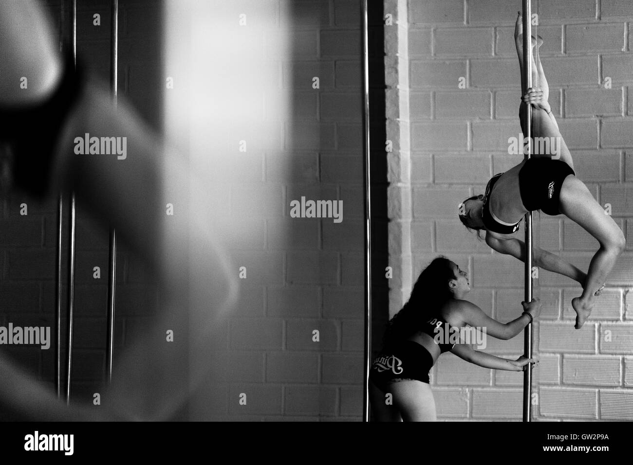 Carolina Echavarria assists Valeria Aboultaif while she performs during a pole dance training session in Academia - Stock Image