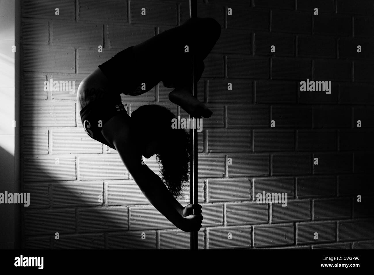 Carolina Echavarria, a young Colombian pole dancer, demontrates her flexibility during a pole dance training session - Stock Image