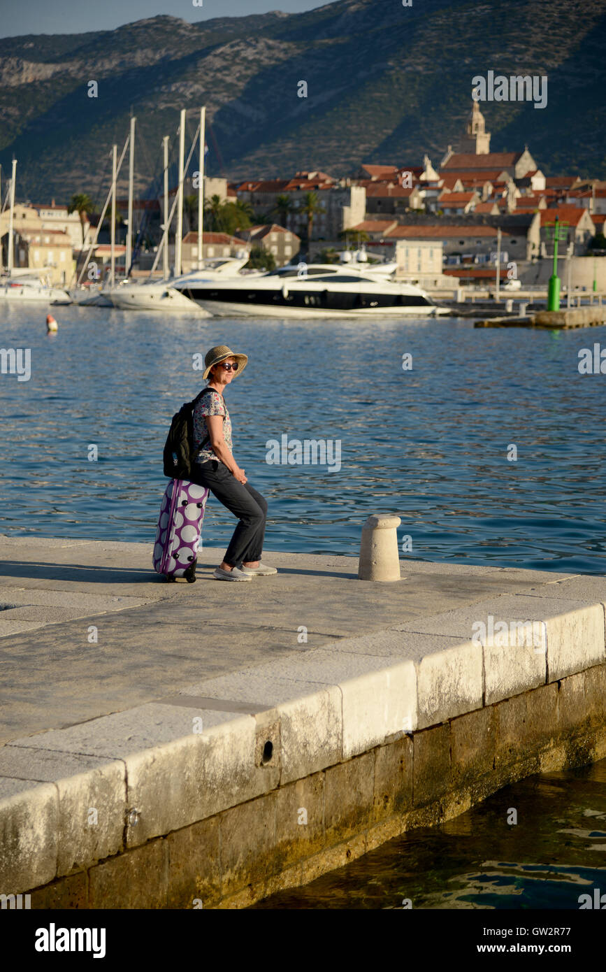 A holidaymaker waits on the quayside for a ferry at Korcula harbour, Croatia. - Stock Image