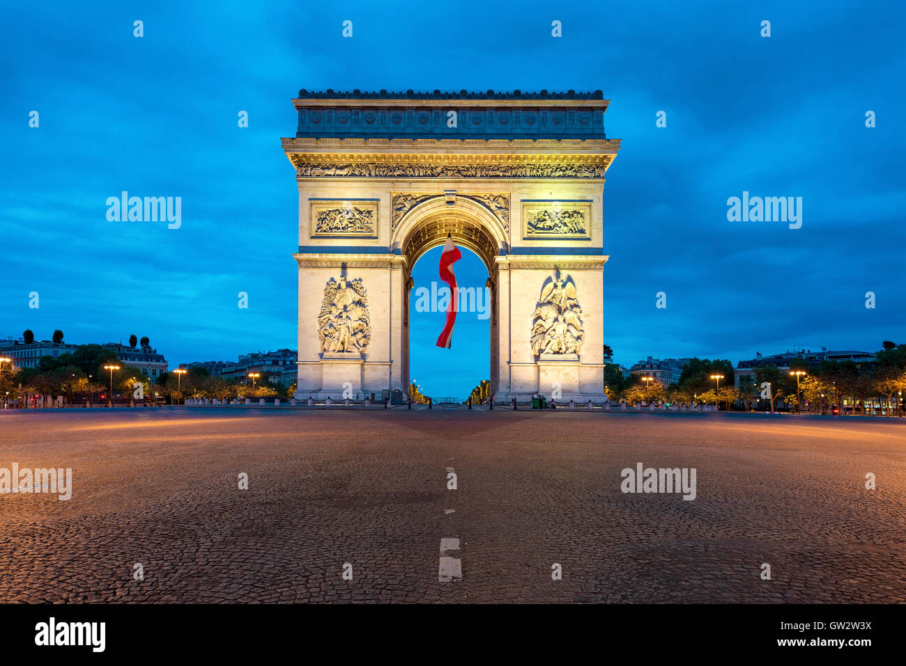 Arc de Triumph Paris and Champs Elysees with a large France flag flying under the arch in Europe victory day at - Stock Image