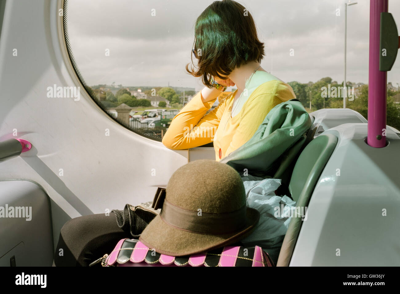 Young fashionable girl looking out of the window travels on top deck of bus - Stock Image
