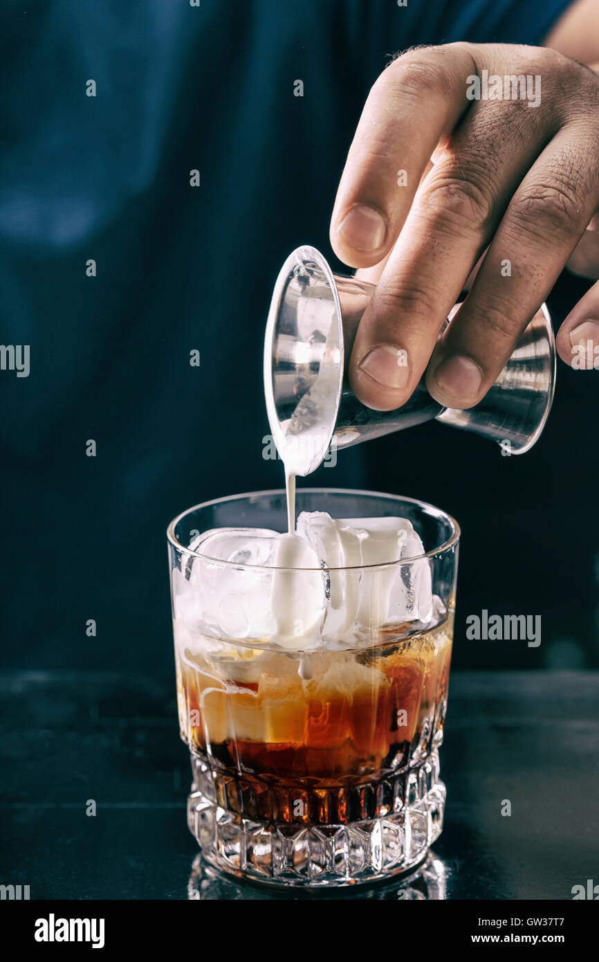 Barman making white russian cocktail at night club - Stock Image