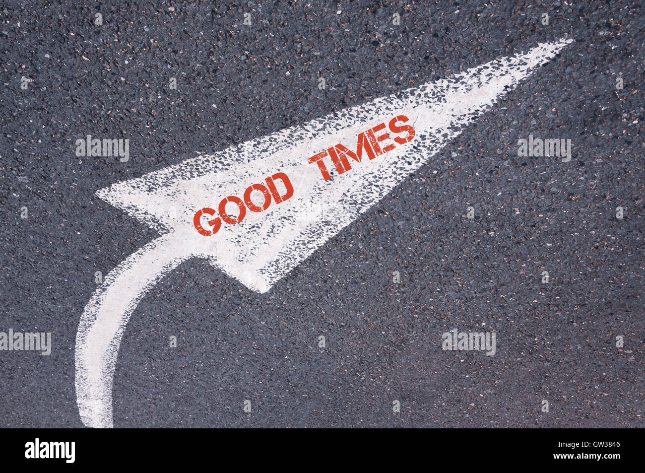 Directional white painted arrow with words GOOD TIMES over road surface, concept image - Stock Image