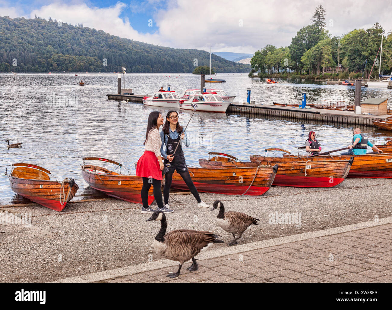 Two Asian girls taking photos with a selfie stick on the shores of Lake Windermere, Cumbria, England, UK - Stock Image