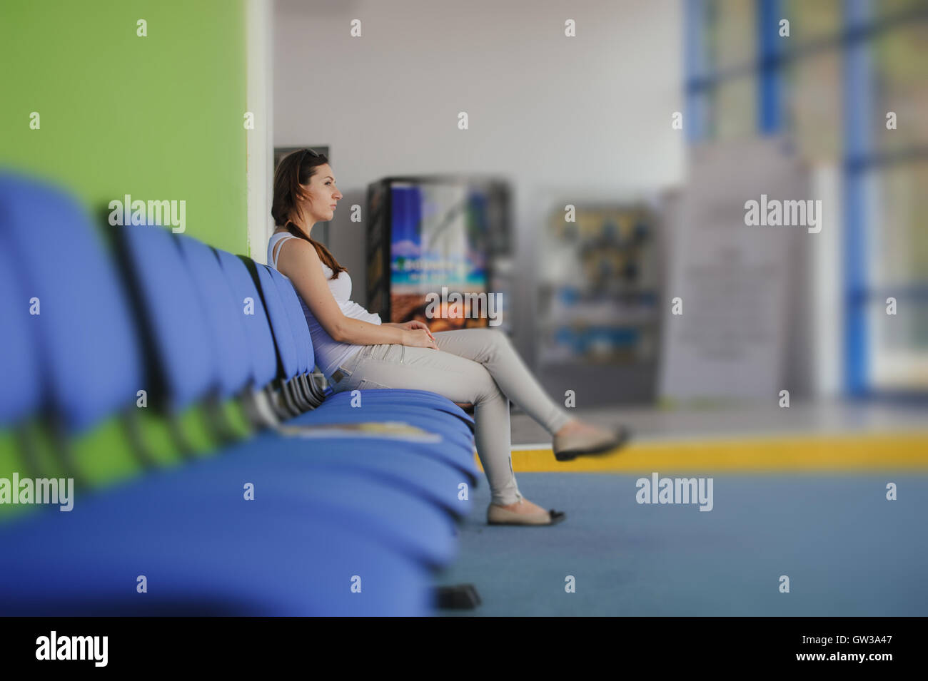 young brunette girl waiting at the airport - Stock Image