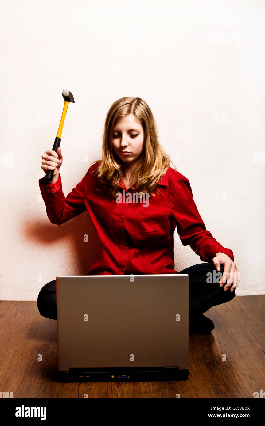 tween girl wanting to destroy her laptop with a hammer - Stock Image