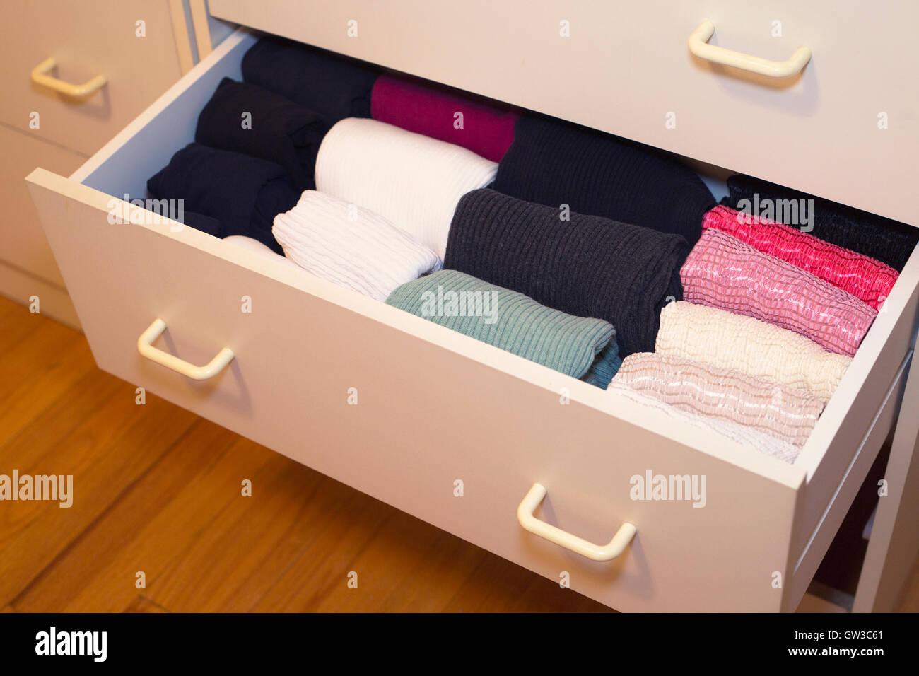 Woman's shirts in a bureau drawer folded in the KonMari method of home organization expert Marie Kondo. - Stock Image