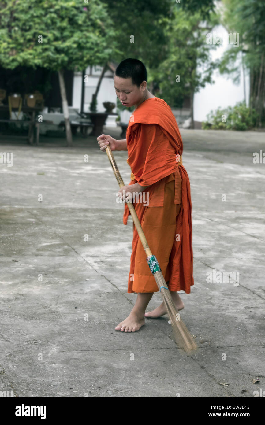 Young saffron-robed monk sweeping the Wat Sene temple courtyard, Luang Prabang, Laos - Stock Image