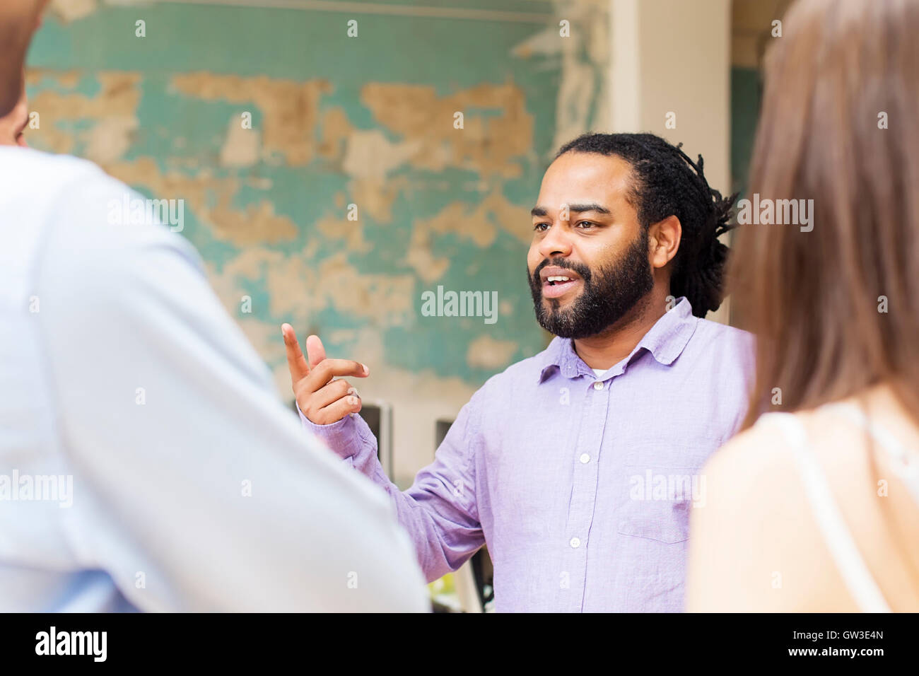 Young African American man talking something to other young people in the office - Stock Image