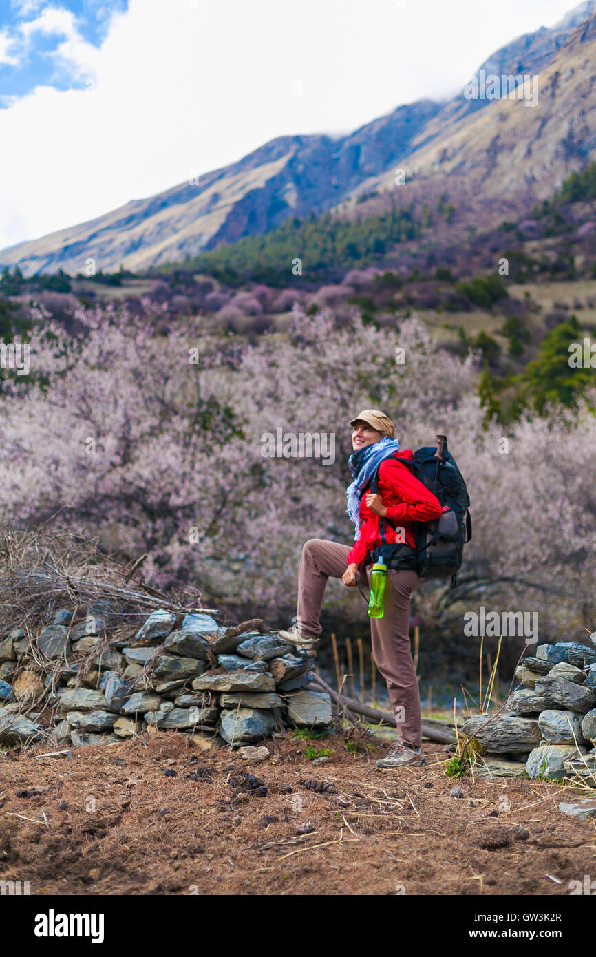 Young Pretty Woman Wearing Red Jacket Backpack Trail Mountains.Mountain Trekking Rocks Path Landscape View Background. - Stock Image