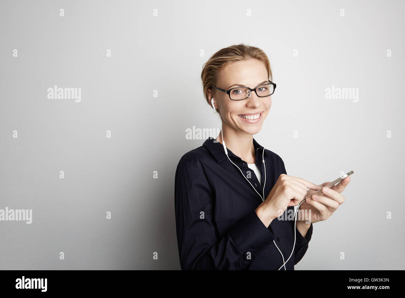 Portrait Handsome Young Woman Glasses Listening Music Smartphone Mobile Headphones Blank White Background.Pretty - Stock Image