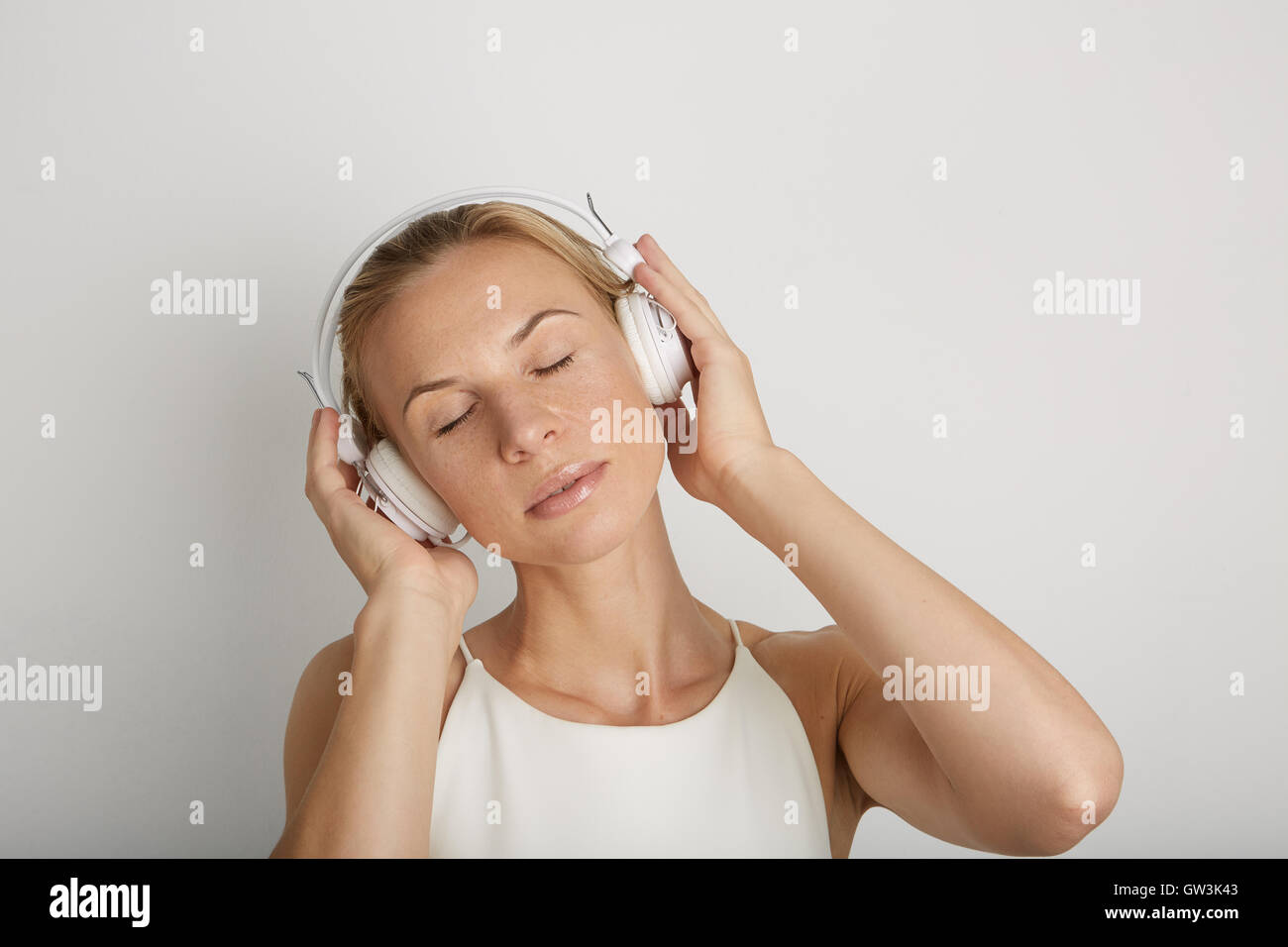 Portrait Handsome Young Woman Listening Headphones.Dreaming Music Player Blank Yellow Color Background.Pretty Girl - Stock Image