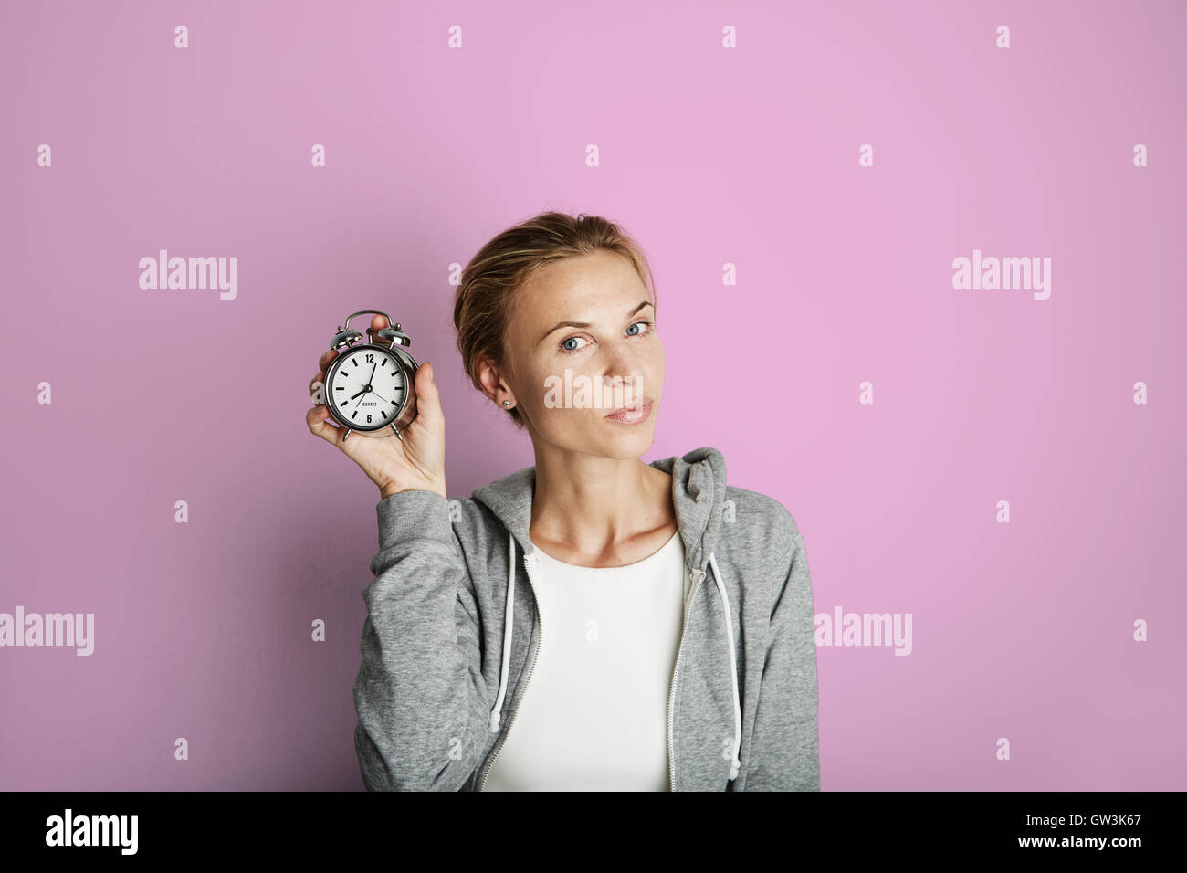 Portrait Handsome Young Woman Posing Blank Pink Background.Pretty Girl Smiling Holding Vintage Alarm Clock Hand - Stock Image
