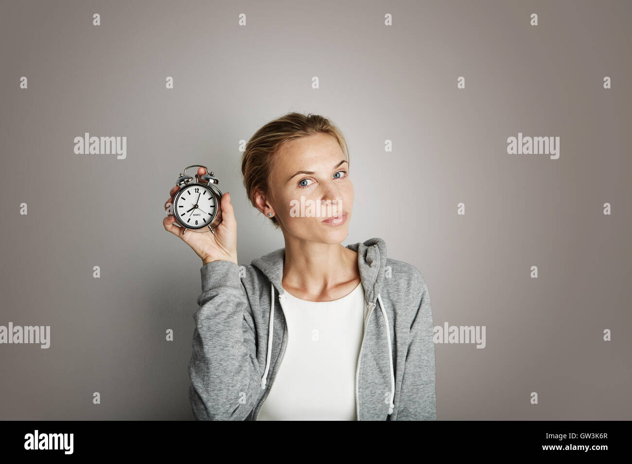 Portrait Handsome Young Woman Posing Blank Gray Background.Pretty Girl Smiling Holding Vintage Alarm Clock Hand - Stock Image