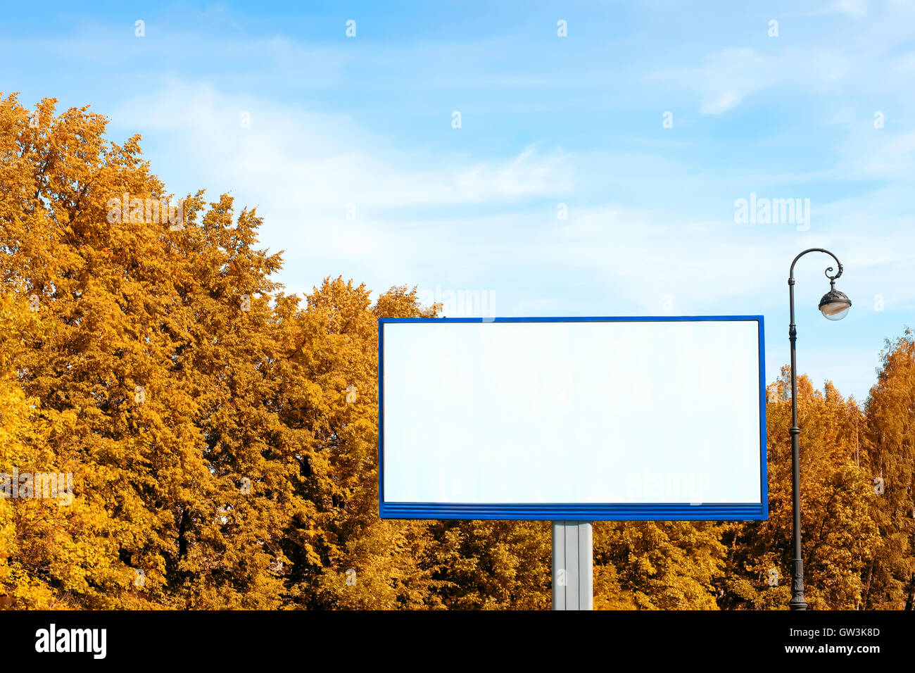 Empty billboard with copy space against bright autumn foliage and blue sky - Stock Image