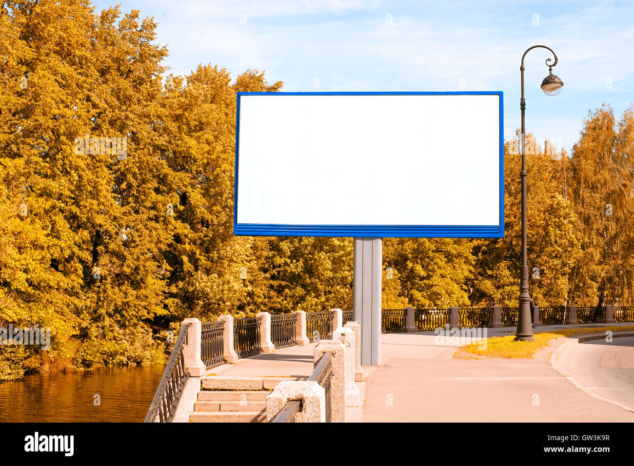 Empty billboard with copy space in autumn city against foliage and blue sky - Stock Image