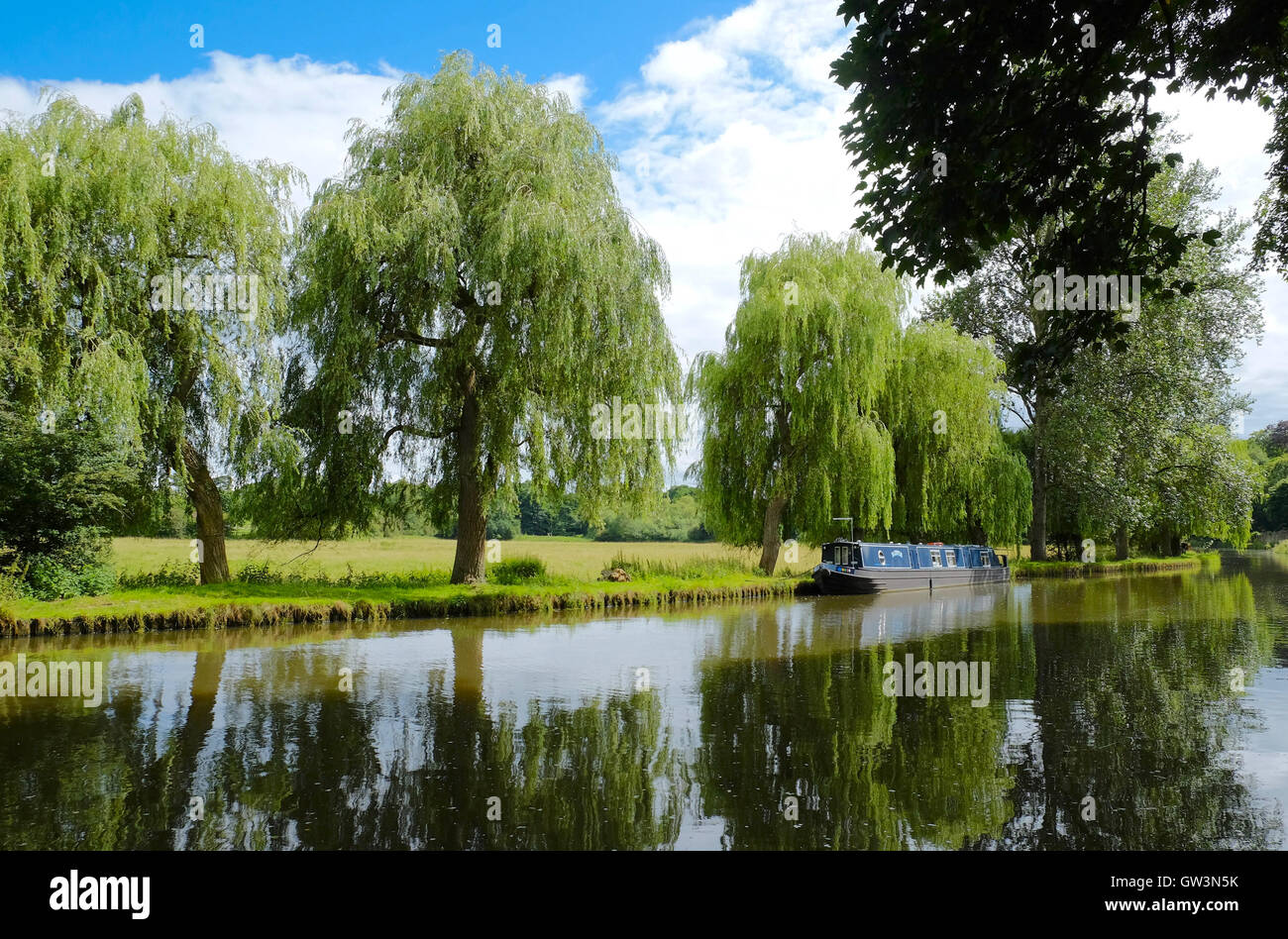 Beautiful view of a Longboat on still reflective waters on the River Wey in Guildford in Surrey. - Stock Image