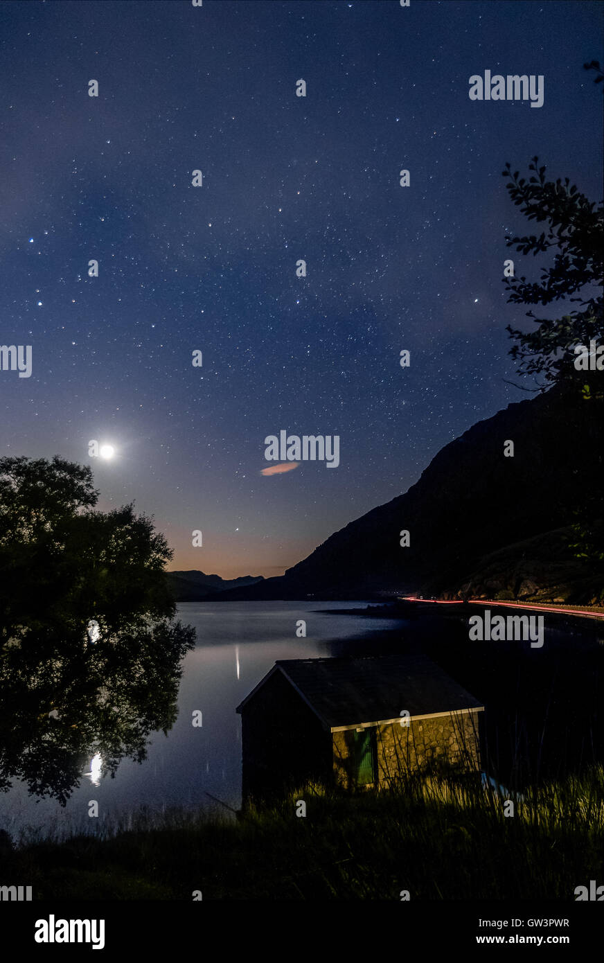 View of Llyn Ogwen Lake at night before sunrise with blu sky, moon and stars. House in the lake and tree. - Stock Image