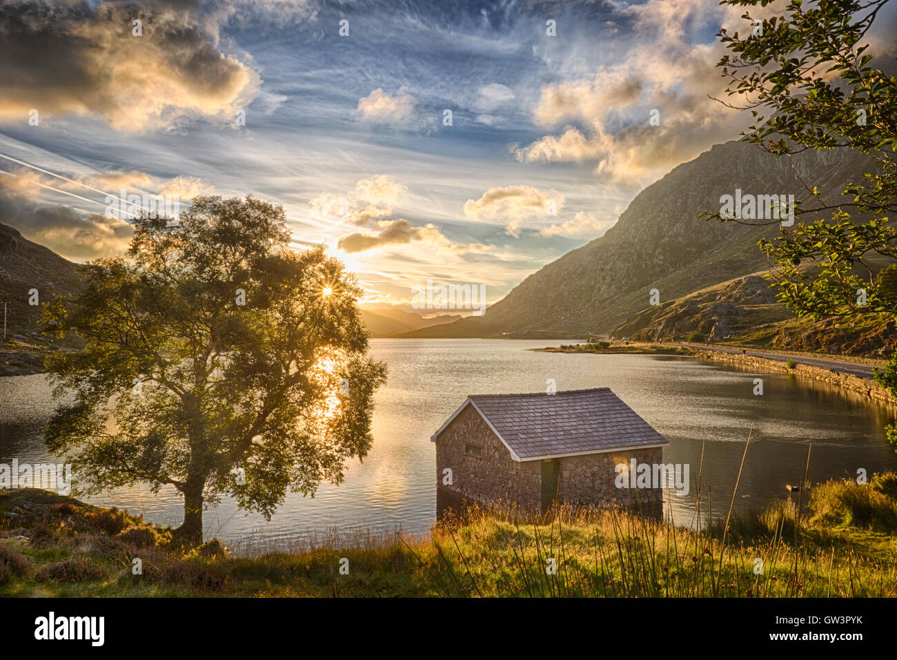 View of Llyn Ogwen Lake at sunrise with blu sky. House in the lake and tree. Stock Photo