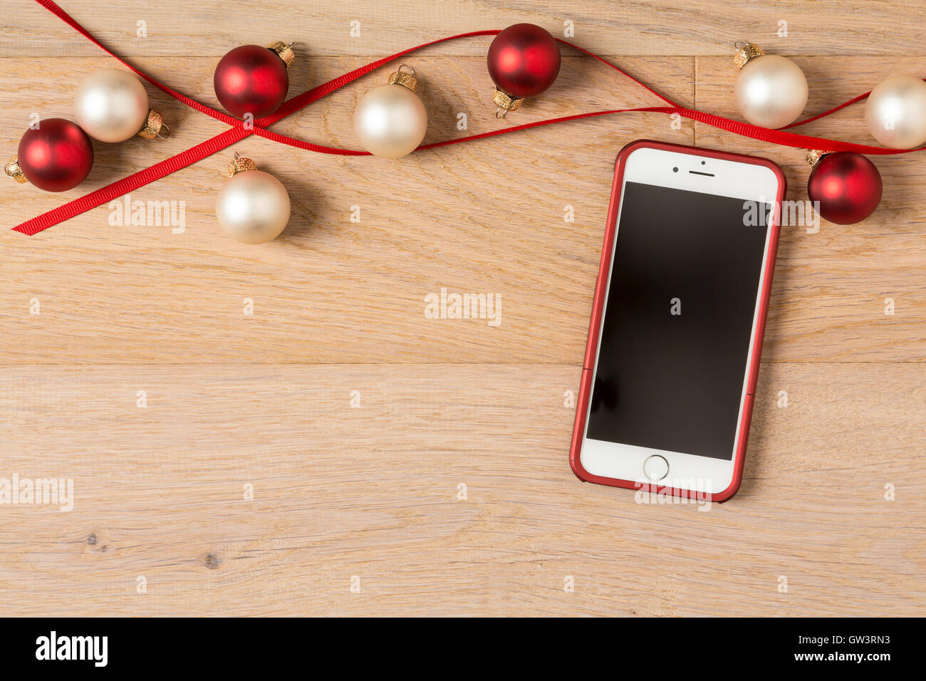 Cell Phone IPhone 6 With Festive Holiday Christmas Decorations On Rustic Wood Background