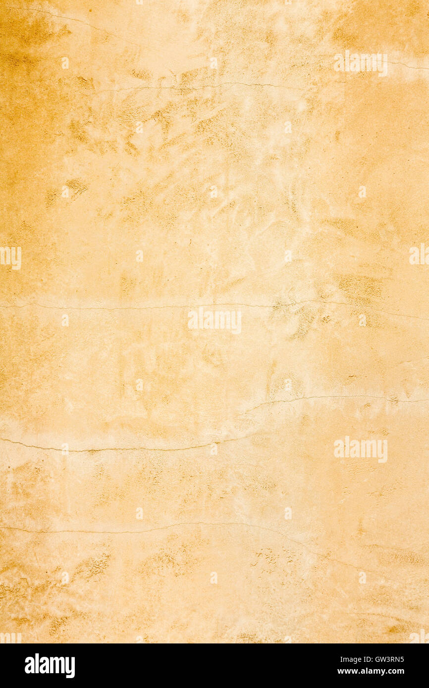 Rustic old aged gold stucco wall distressed vertical background texture - Stock Image