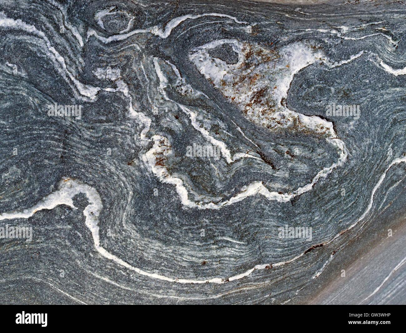 Swirls and folds of white quartz or marble veins in grey rock strata, Uragaig, Isle of Colonsay, Scotland, UK. - Stock Image