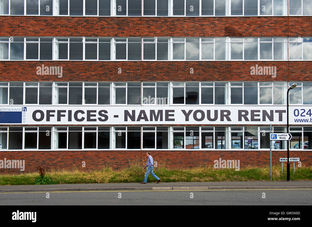 Man walking past office block with banner: Offices, Name Your Rent - Stock Image